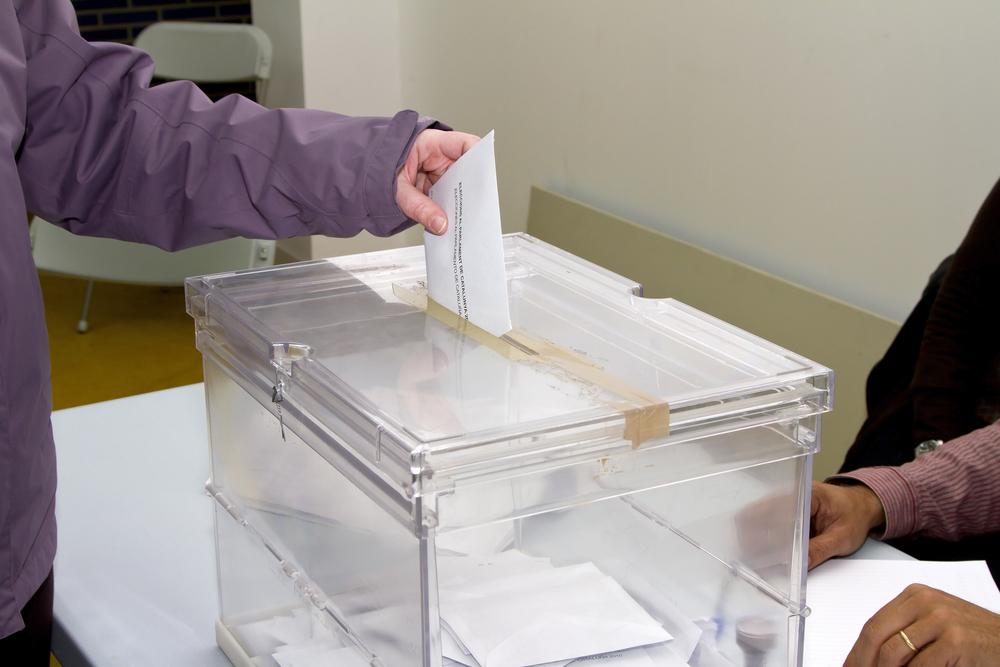 Detalle de persona introduciendo su voto en una urna. Elecciones